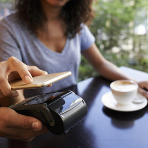 Woman using NFC technology when paying in restaurant