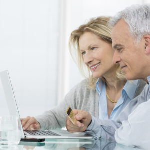 Portrait Of Senior Couple Shopping Online With Credit Card