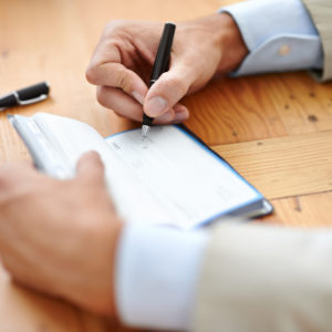 Cropped closeup shot of a businessman signing cheques