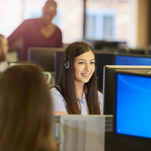 a female customer service representative sits at her computer terminal in a call centre chatting happily over her headset to a customer. In the background and foreground colleagues are seen sitting at their desks .