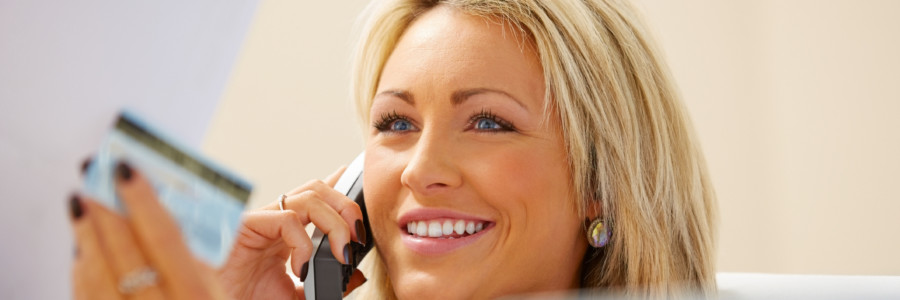 Smiling young woman holding credit card bill and talking on phone at home
