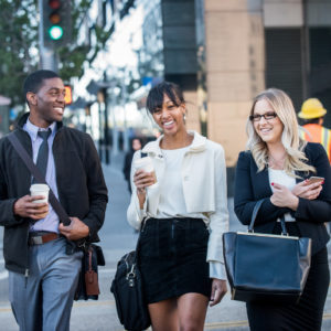 A young African American male and female and a blonde caucasian female business associates or colleagues, crossing a city street at the end of their work day with coffee.